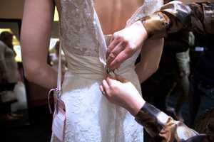 A volunteer helps a bride try on a gown.