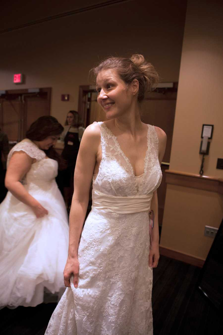 An unidentifiedbride asks a friend for advice when she tries on a gown.