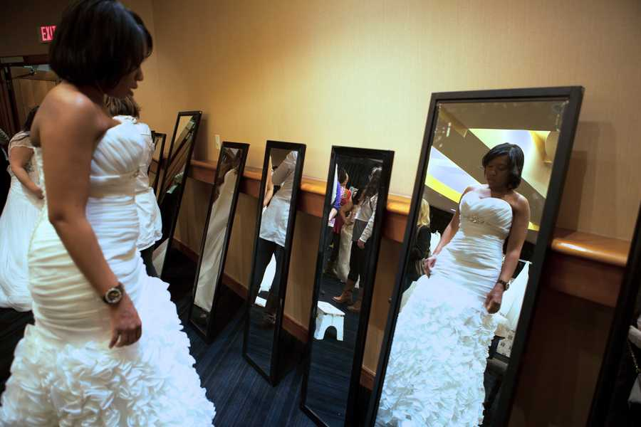 An unidentified bride-to-be looks at the mirror with other brides in a large fitting room.