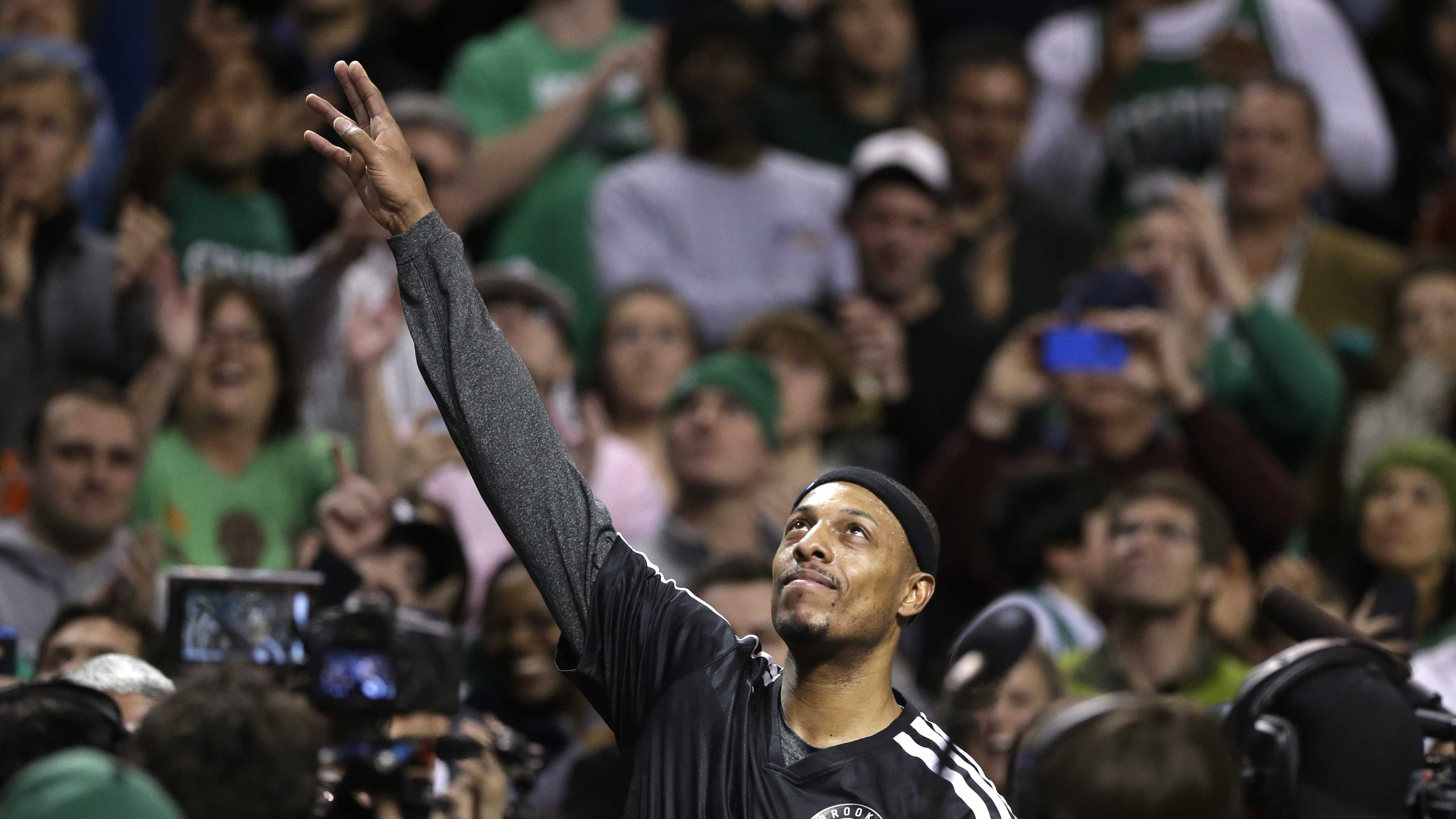 Brooklyn Nets forward Paul Pierce, center, formerly of the Boston Celtics, waves to the crowd during a tribute to him in an NBA basketball game against the Boston Celtics, Sunday, Jan. 26, 2014, in Boston.