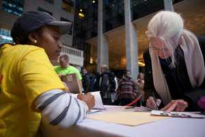 """Berlyn Olibrice (left), a member of """"ClimbCorps"""" helps Patricia Sabbey, 66, to register for the climbing a few minutes before it starts."""