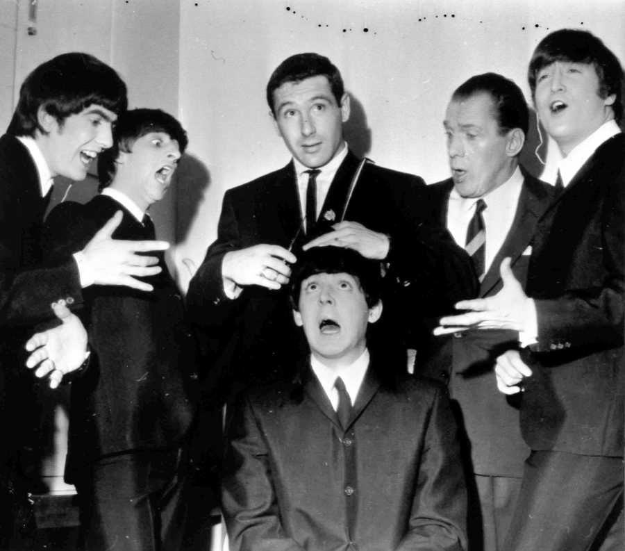 American speed skating champion Terry McDermott, top center, a barber by trade, pretends to take a swipe at the famed locks of Paul McCartney to the mock horror of the other Beatles and Sullivan during rehearsals.