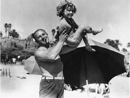 Shirley Temple, 5-year-old screen actress, is shown with her father, George F. Temple, as they enjoy a day at the beach at the Santa Monica Athletic Club in Santa Monica on June 5, 1934 .