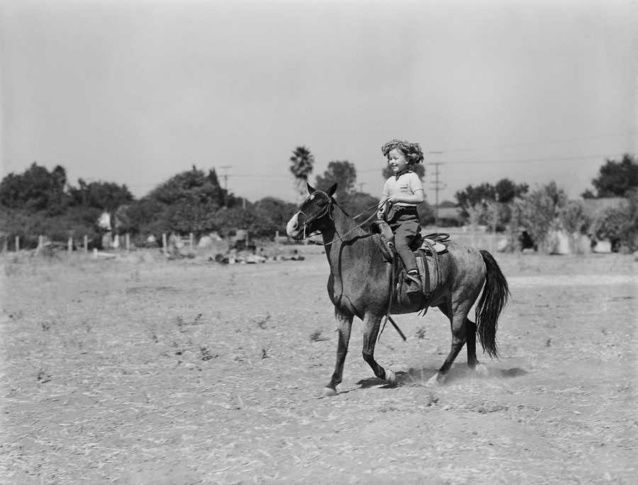 Shirley Temple, child star of the screen, tries out her newest pony, Road King 11, champion trick pony of the American Royal Horse show in Kansas City two years ago on Oct. 21, 1936. The animal was given Shirley by Betsy King Ross, trick rider, as a companion to the little actress other pony, Spunky.