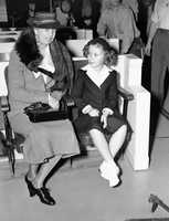 Mrs. Eleanor Roosevelt, first lady of the nation, and Shirley Temple, first lady of the motion picture box office, are shown as they talked together when Mrs. Roosevelt visited the set where Shirley is making her latest picture, Little Miss Broadway, March 18, 1938, Hollywood, Calif.