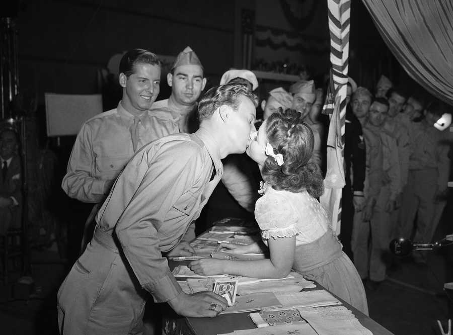 """For the first time in her long movie career, Shirley Temple gets kissed in grown-up fashion by Jerry Shane, an ex-Marine from Grand Rapids, Mich., who plays a bit part in the movie called """"Kiss and Tell,"""" Jan. 19, 1945."""