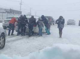 A group of people push a stuck car on Route 1 in Saugus.