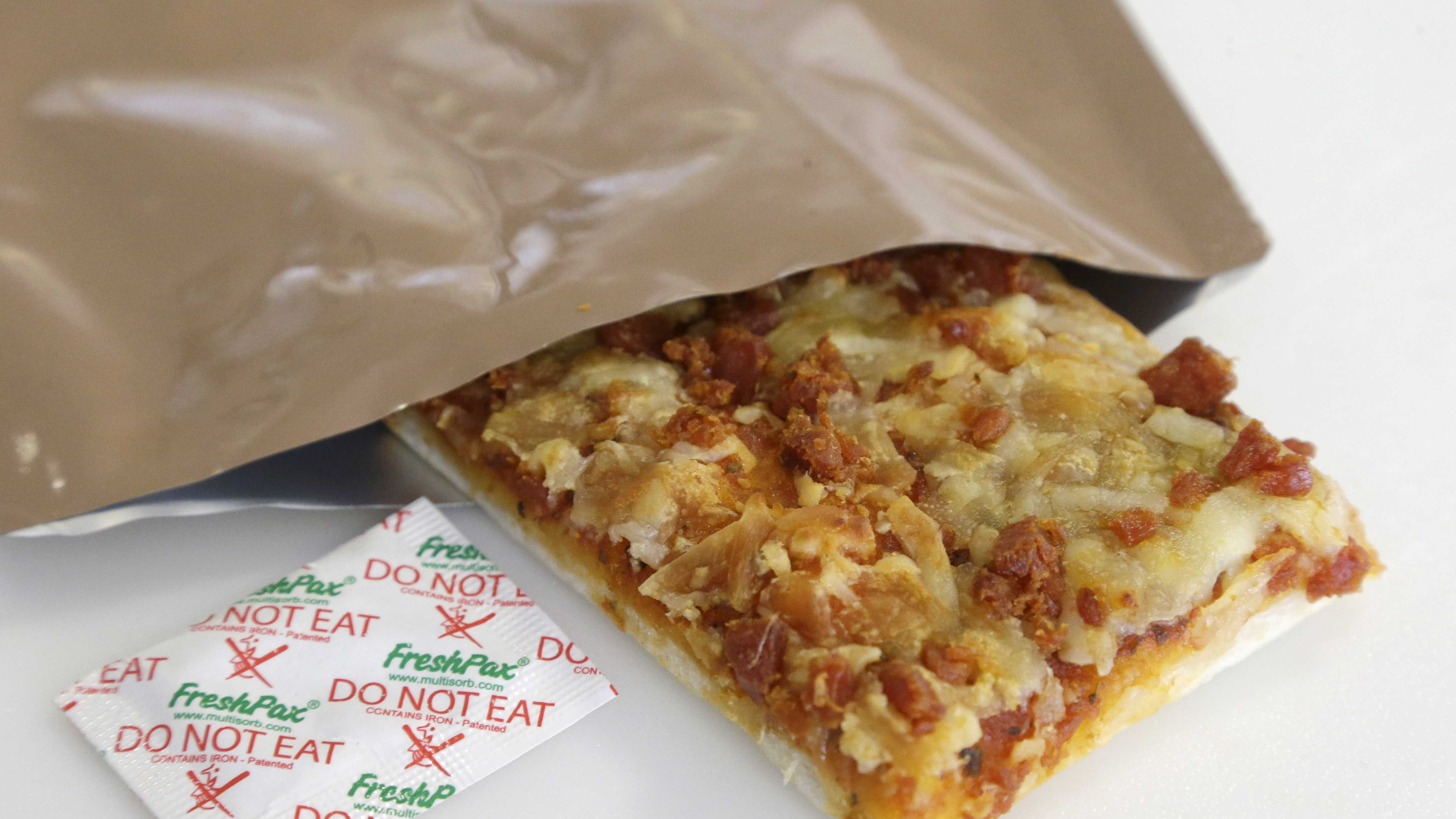 A slice of prototype pizza, in development to be used in MRE's — meals ready to eat, sits in a packet next to a smaller packet known as an oxygen scavenger, left, at the U.S. Army Natick Soldier Research, Development and Engineering Center.