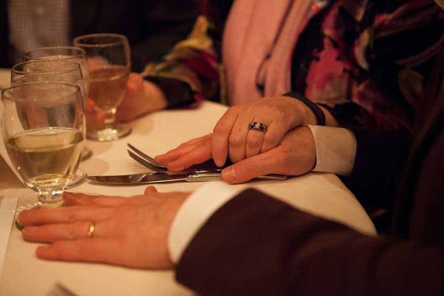 """After being blindfolded, Claude Cicchetti keeps his hands on his fork and knife all the time, in case he can't find them. His wife, Robin Cicchetti holds his hand. """"Am I holding your hand?"""" Inna P. Grant asks her husband Greg Grant at the same table."""