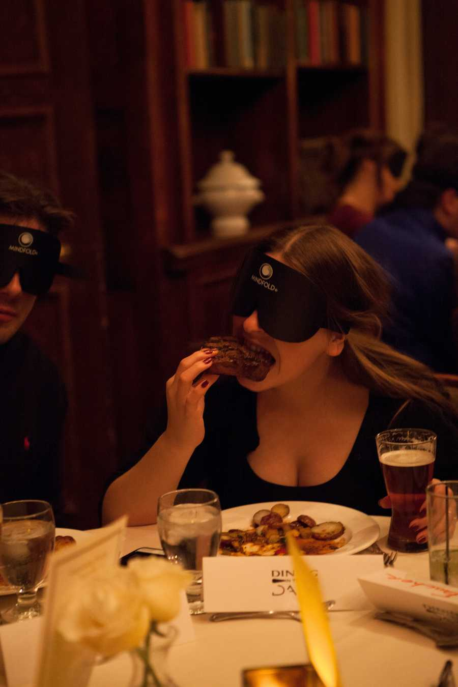 """A guest uses her hand to eat steak. """"Everyone is blindfolded and acting the same way. No one thinks you are foolish,"""" said Ripperger."""