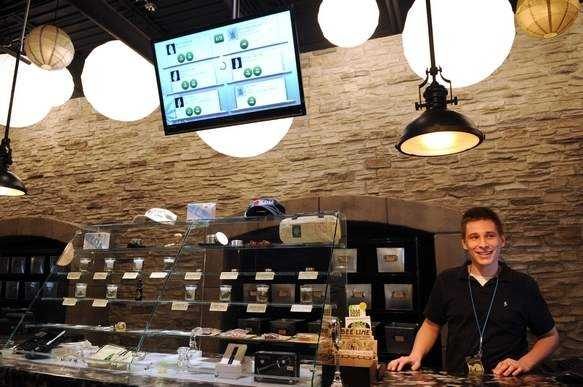 The center's sales area features modern, glass display cases with an array of marijuana products, including dried buds, extracts and edible items.