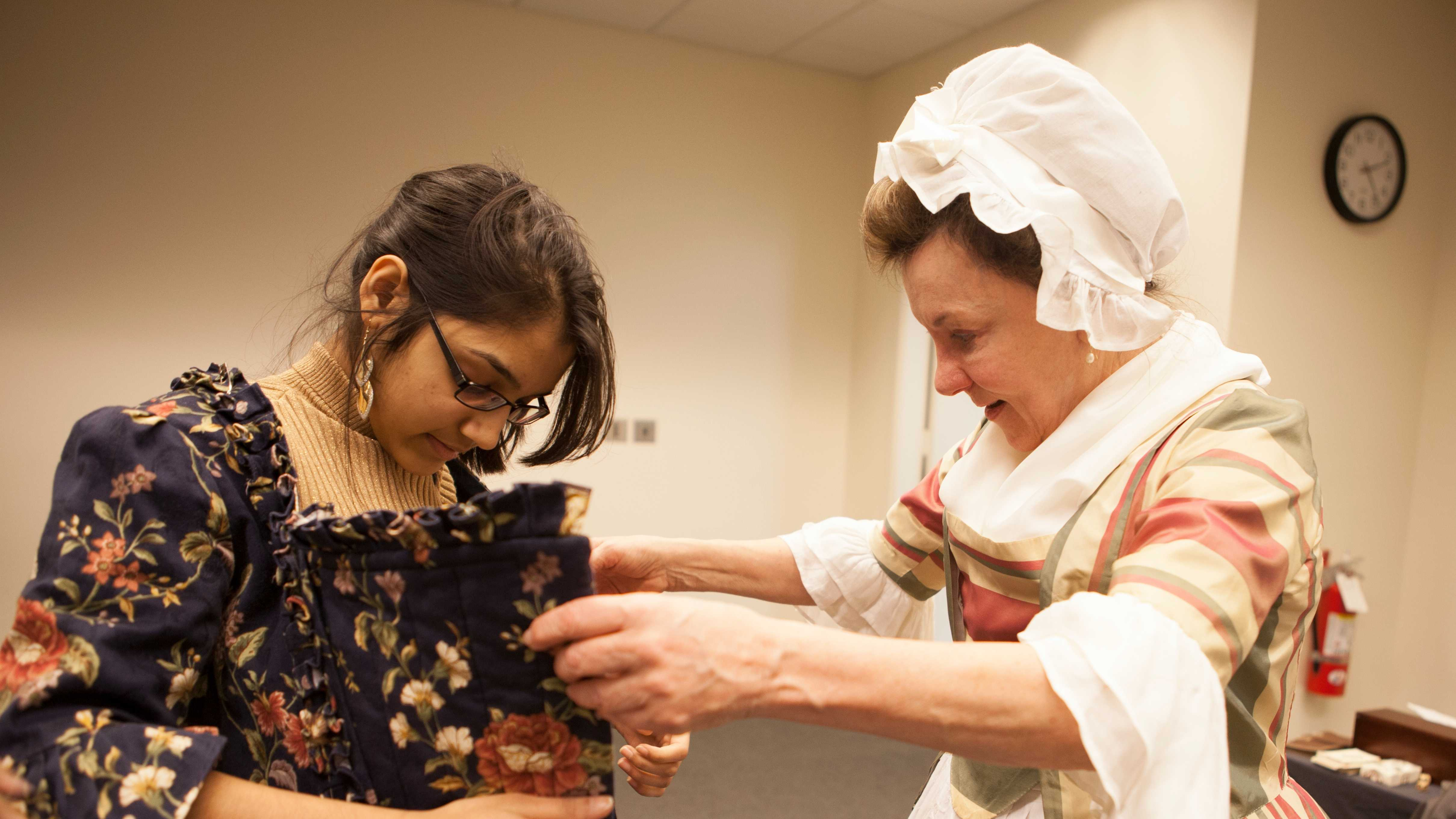 "Astha Agarwal, (left), a senior from Newton South High school tried on clothes from the 18th Century with the help of ""First Lady Abigail Adams,"" portrayed by Patricia Bridgman."