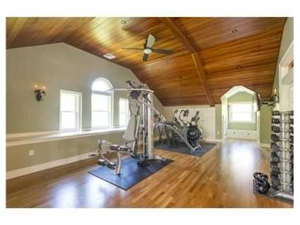 Anincredible 3rd floor great room with projection screen, wet bar and a cherry wood ceiling.
