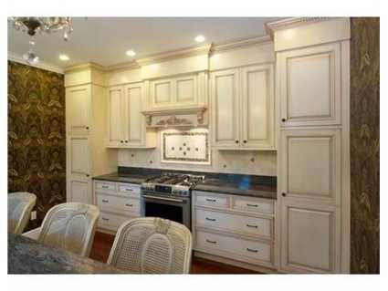 It has custom cabinets, granite counters with a large center island that adjoins a spacious breakfast area.