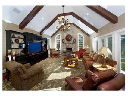 Sun filled cathedral ceiling family room w fireplace and custom built ins.