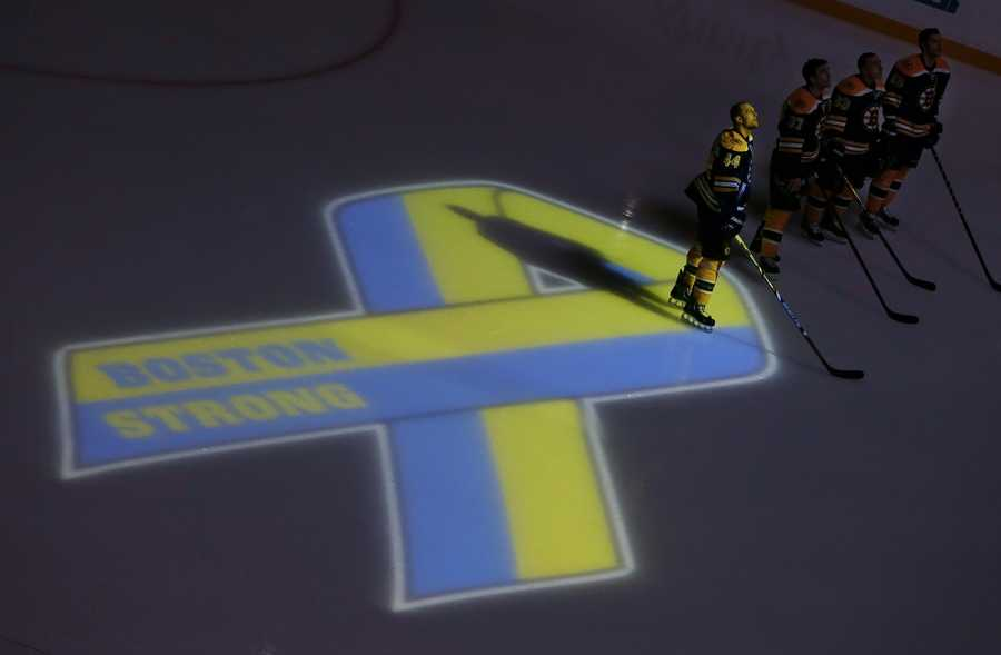 Boston Bruins hockey starters stand next to a ribbon projected onto the ice at TD Garden in Boston, Wednesday, April 17, 2013, during a pregame ceremony in the aftermath of Monday's Boston Marathon bombings.