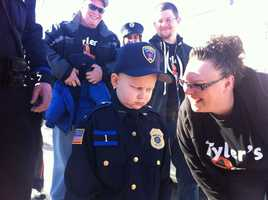 Tyler leaves his house in uniform, with his mother, Rachel, and police.