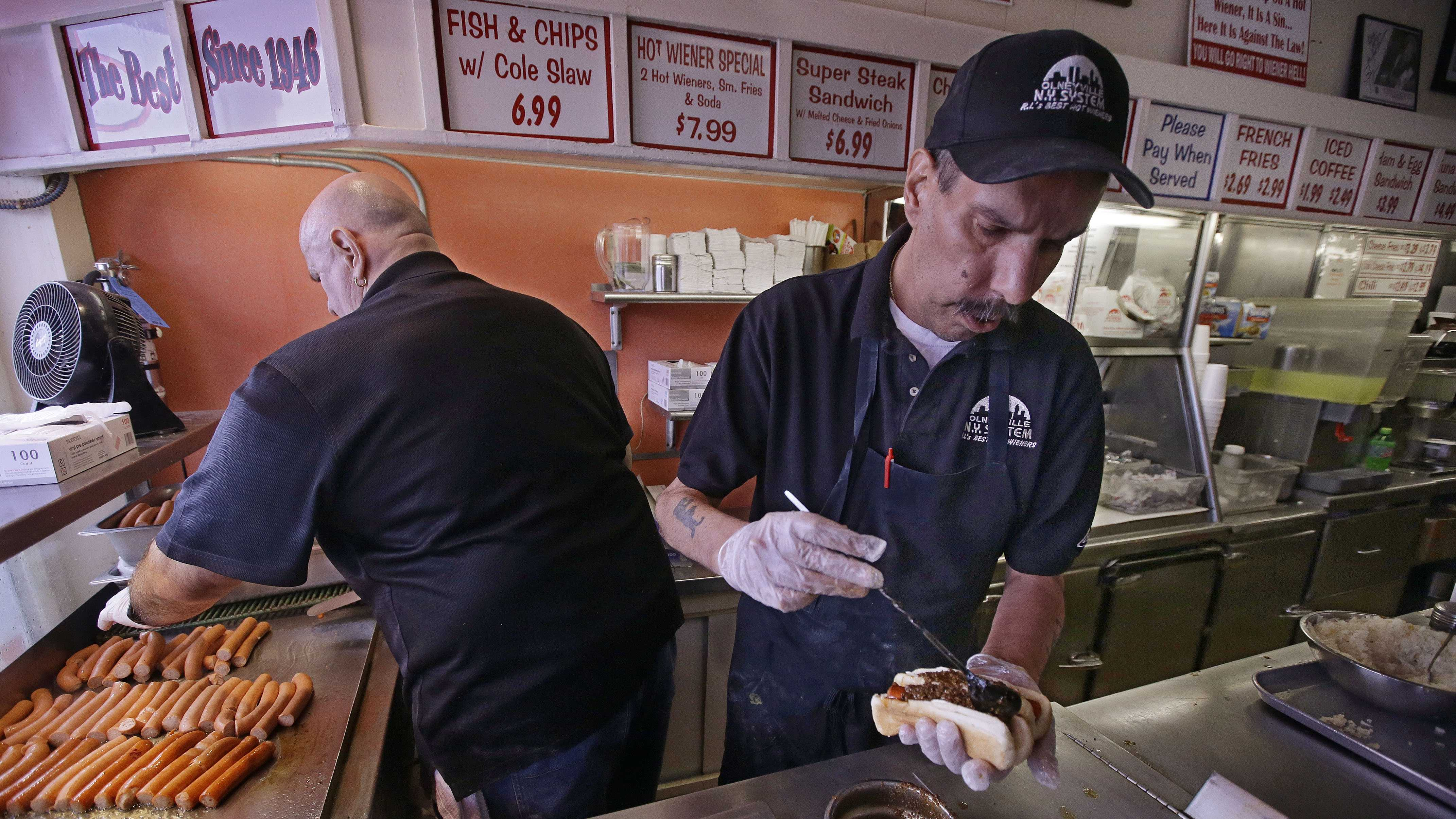 "In this Monday, March 3, 2014 photo manager Jimmy Saccoccio works the grill as Sal O'Brien preps a hot wiener ""all the way"" at Olneyville New York System of Providence in Providence, RI. The James Beard Foundation named the Rhode Island restaurant one of five ""American Classics"" this year as best known for hot wieners, also called hot dogs."