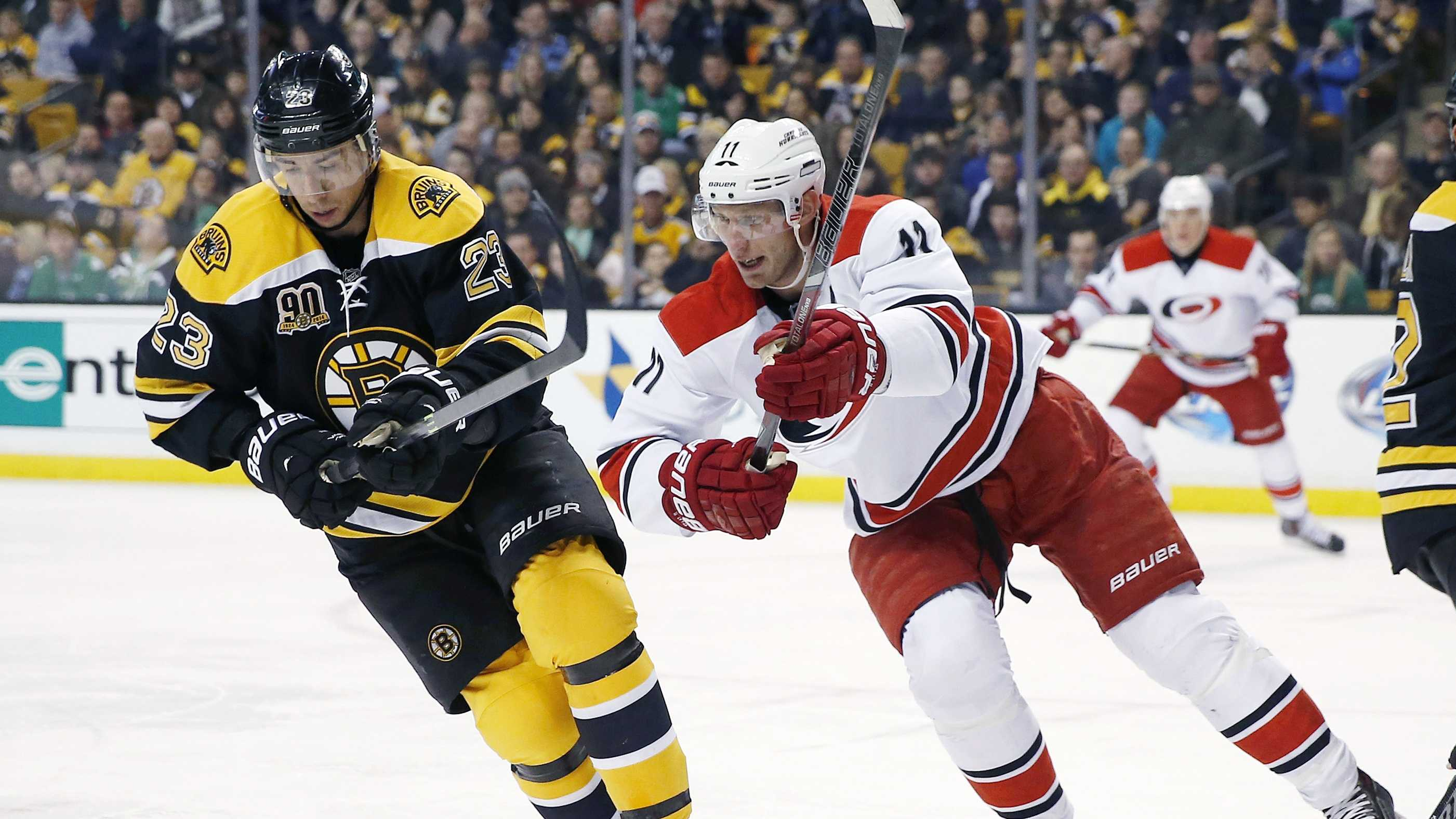 Boston Bruins' Chris Kelly (23) and Carolina Hurricanes' Jordan Staal (11) battle for the puck in the first period of an NHL hockey game in Boston, Saturday, March 15, 2014.