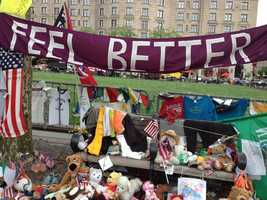 """""""Feel Better"""" sign along with T-shirts and stuffed animals at the Copley Square Memorial for the 2013 Boston Marathon."""