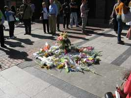 Makeshift memorial in front of the Boston Public Library. Includes flowers, flags, and a marathon medal.