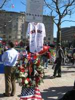 """A photograph of the memorial in Copley Square with a wreath, American flags, and a Red Sox jersey inscribed with """"4/15/13 will always be in our hearts"""" and the names of the victims"""