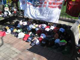 """Photograph of a collection of Red Sox, Bruins, Patriots and other hats, many with inscriptions, at the Copley Square memorial. A """"Boston Strong"""" poster with handwritten notes hangs in the background."""