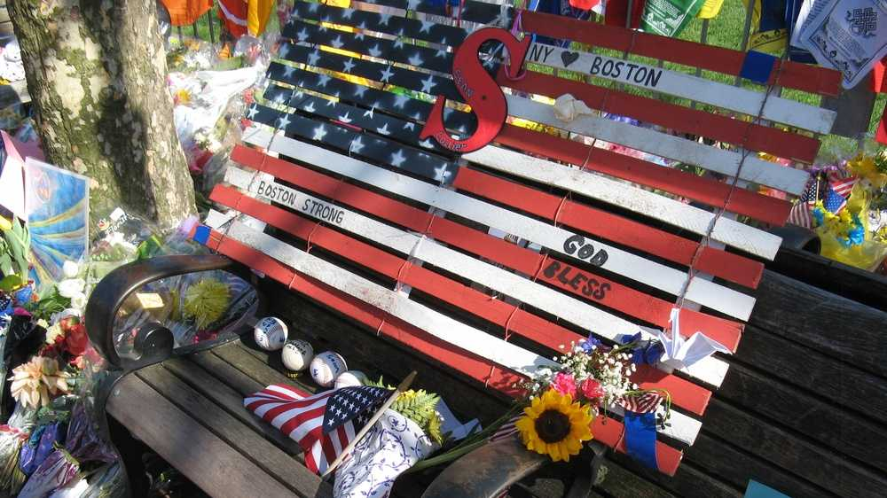 "An American flag made from what appears to be wooden boards and wire, at the Copley Square memorial. Inscriptions include ""NY loves Boston,"" ""Boston Strong,"" ""God Bless,"" and ""Sean Collier."" Baseballs, flags and flowers are also visible."