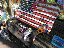 """An American flag made from what appears to be wooden boards and wire, at the Copley Square memorial. Inscriptions include """"NY loves Boston,"""" """"Boston Strong,"""" """"God Bless,"""" and """"Sean Collier."""" Baseballs, flags and flowers are also visible."""