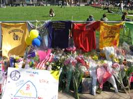 """A row of T-shirts and flowers along a fence at the Copley Square memorial. Shirts include """"Boston College Newton Fan,"""" """"Mass General Cystic Fibrosis Marathon Team,"""" and """"Gloucester."""""""