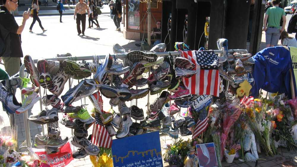 "A section of fence hung with running shoes, signs, and flowers at the Copley Square memorial. A sign in the foreground reads: ""These people tried to make life bad for the city of Boston, but all they can ever do is show just how good those people are. -Stephen Colbert"""