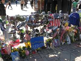 """A section of fence hung with running shoes, signs, and flowers at the Copley Square memorial. A sign in the foreground reads: """"These people tried to make life bad for the city of Boston, but all they can ever do is show just how good those people are. -Stephen Colbert"""""""