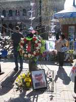 """Flower wreaths, flags and paper cranes hung on a tree at the Copley Square memorial. A framed poster at the base of the tree reads: """"Boston Strong Forever Fearless Bostonians United."""""""