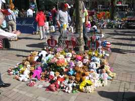 Photograph of crosses bearing the names of Martin Richard, Lingzi Lu, and Krystle Campbell, along with their pictures, at the Copley Square memorial. The crosses are surrounded by stuffed animals and flowers