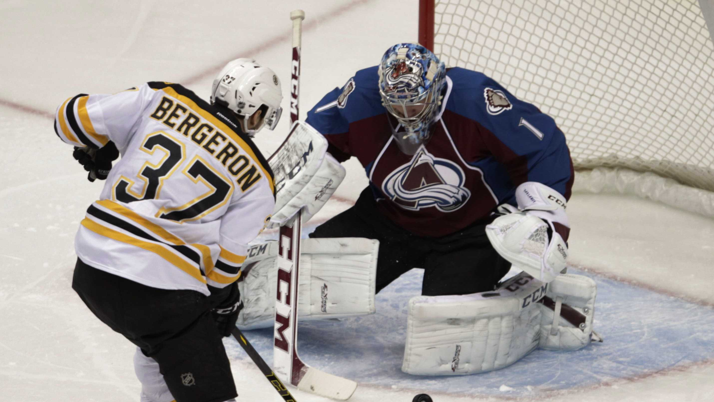 Boston Bruins center Patrice Bergeron (37) scores on Colorado Avalanche goalie Semyon Varlamov (1) the first period of an NHL hockey game in Denver on Friday, March 21, 2014.