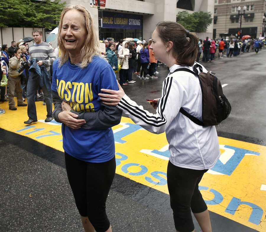 Pam Vingsness, right, comforts her crying mother, Rachel, of Newton, Mass., after they crossed the finish line, as runners who were unable to finish the Boston Marathon on April 15 because of the bombings were allowed to finish the last mile of the race in Boston, May 25, 2013.