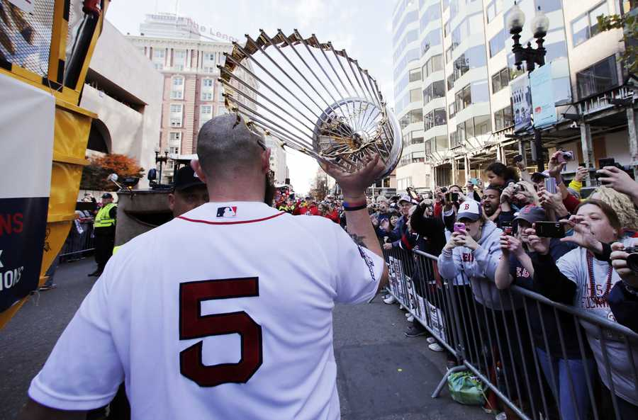 Boston Red Sox's Jonny Gomes carries the 2013 World Series trophy and a team jersey to the finish line of the Boston Marathon, in honor of those affected by the bombings, as they stopped the parade in celebration of the baseball team's World Series win, Nov. 2, 2013, in Boston.