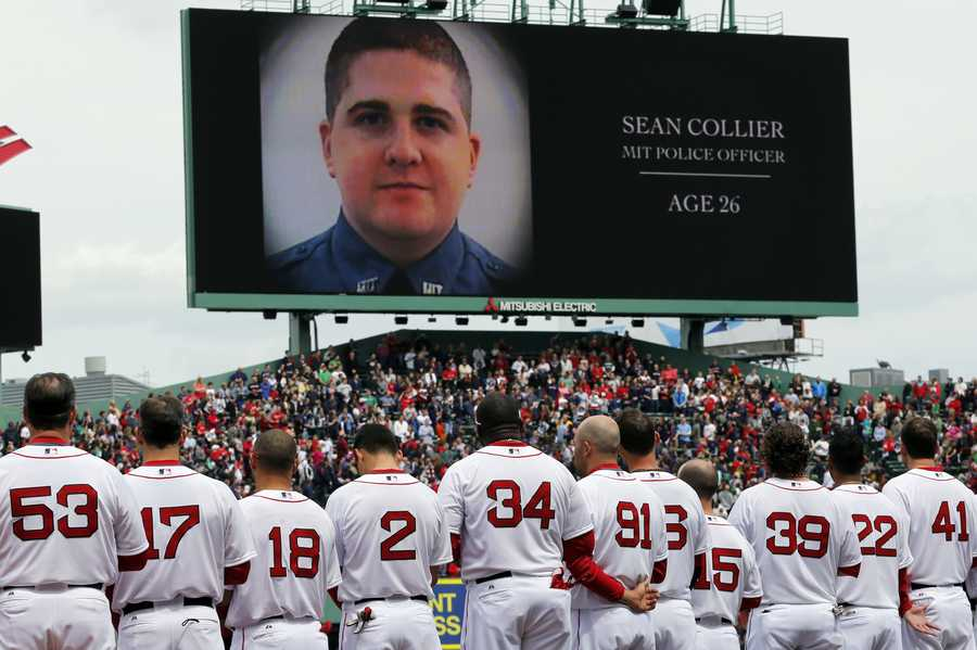 The Boston Red Sox line up during a tribute to victims of the Boston Marathon bombing and its aftermath, as an image of MIT Police Officer Sean Collier is displayed on the scoreboard, before a baseball game against the Kansas City Royals in Boston, Saturday, April 20, 2013.