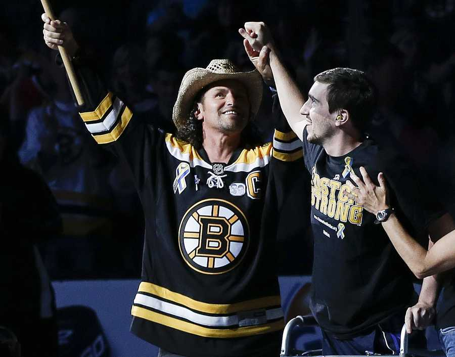 Standing on artificial legs, Boston Marathon bombing victim Jeff Bauman and Carlos Arredondo, wearing the hat, who assisted him at the scene, waves the Boston Strong banner before Game 6 of the NHL hockey Stanley Cup Finals between the Boston Bruins and the Chicago Blackhawks, June 24, 2013, in Boston.