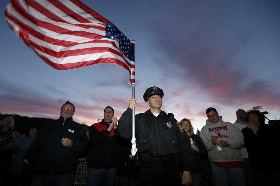 Watertown Police officer Brandon O'Neill, center, holds a U.S. flag during a vigil for the victims of the Boston Marathon bombing, Saturday, April 20, 2013, in Watertown, Mass., the day after suspected bomber Dzhokhar Tsarnaev was captured.