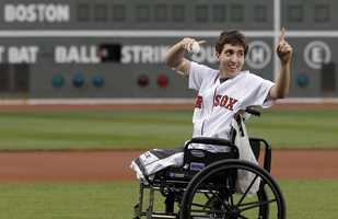 Boston Marathon bombing survivor Jeff Bauman acknowledges cheering fans before throwing out a ceremonial first pitch at Fenway Park prior to a baseball between the Boston Red Sox and the Philadelphia Phillies in Boston, May 28, 2013.