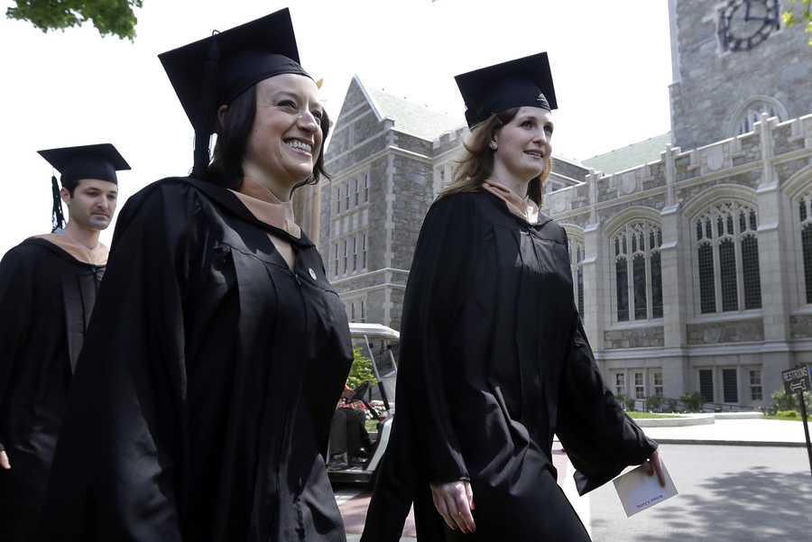 Liza Cherney, left, and Brittany Loring, right, lead the procession of graduates of the Carroll School of Management during commencement ceremonies at Boston College in Boston, Monday, May 20, 2013. The two women were injured in the Boston Marathon bombings on April 15, with Loring needing three operations after her left leg was struck by shrapnel from the first of the twin blasts. Cherney was standing next to her close friend and classmate Loring and was also badly hurt.