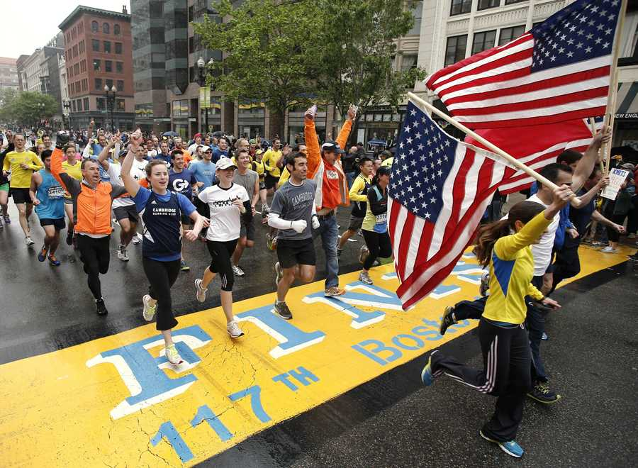 Runners who were unable to finish the Boston Marathon on April 15 because of the bombings cross the finish line on Boylston Street after the city allowed them to finish the last mile of the race in Boston, May 25, 2013.