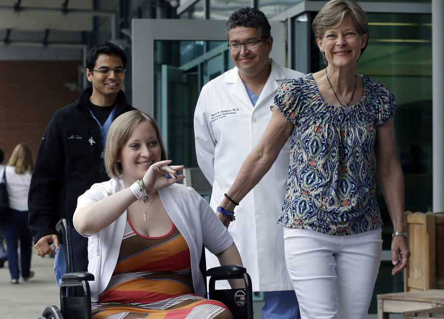Boston Marathon bombing survivor Erika Brannock, 29, a Baltimore area pre-school teacher who lost a leg in the Boston Marathon bombings, is accompanied by her mother, Carol Downing, right, as she is released from Beth Israel Deaconess Medical Center in Boston, June 3, 2013. Brannock and her sister, Nicole Gross, were waiting at the finish line for their mother to finish the race when the bombs went off. Walking behind are Dr. Alok Gupta, left, and Dr. Edward Rodriguez.