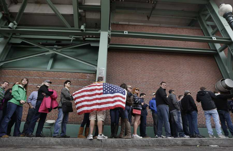 Adam Comeau, 17, holds a U.S. flag as he waits in line to enter Fenway Park before the start of a baseball game between the Kansas City Royals and the Boston Red Sox, the first game held in the city following the Boston Marathon explosions, Saturday, April 20, 2013, in Boston.