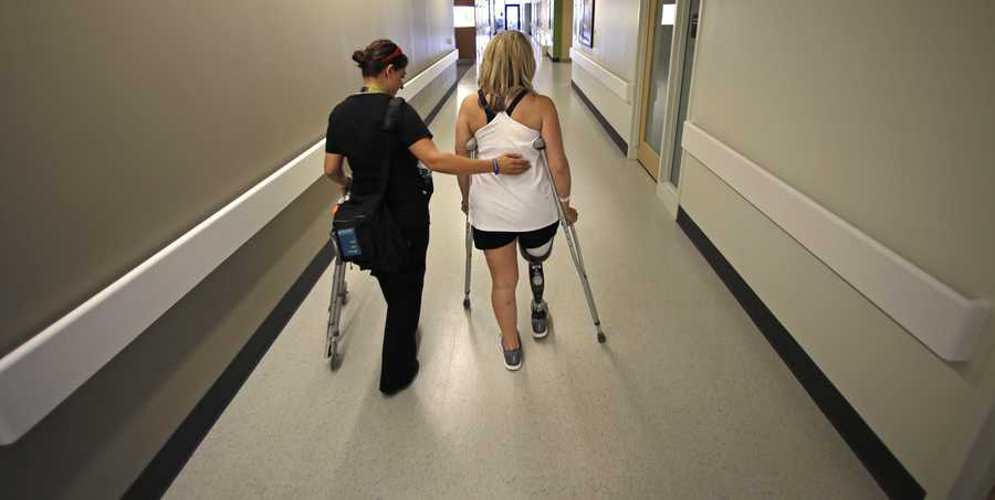 Boston Marathon bombing survivor Roseann Sdoia, of Boston, walks down a long corridor as she is followed by her physical therapist Dara Casparian at the Spaulding Rehabilitation Hospital, June 20, 2013, in Boston. Sdoia went back to the hospital to learn to walk with her new leg.