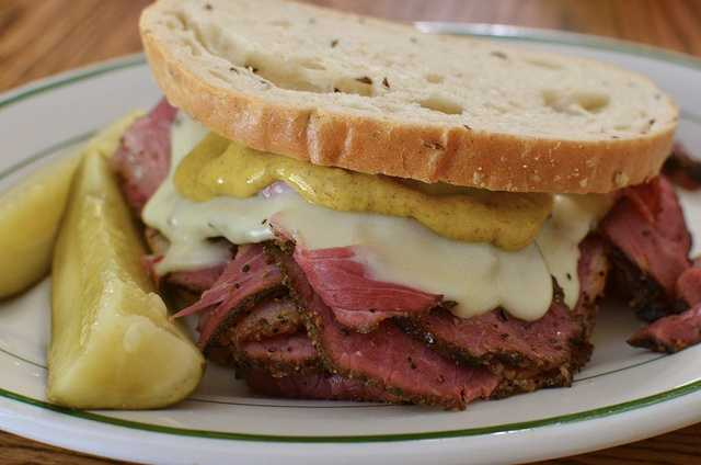 Pastrami on Rye is a straight-forward sandwich, with slices of pastrami on rye bread. However, some people add their own spin on the sandwich. Foodnetwork.com posted the recipe for Emeril Lagasse's favorite pastrami sandwich which includes grilled onions and pastrami simmered in beer and mustard for three minutes. (Photo by Jeffreyw via Flickr)