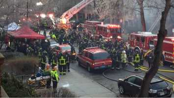 Boston firefighters gather after two of their own were lost in a massive Beacon Street fire on Wednesday.