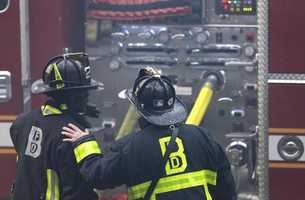 A firefighter places his hand on the shoulder of another at the scene of the fatal fire at a four-story brownstone in the Back Bay neighborhood near the Charles River, Wednesday, March 26, 2014 in Boston.