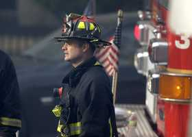 A firefighter looks on at the scene of the fatal fire at a four-story brownstone in the Back Bay neighborhood near the Charles River, Wednesday, March 26, 2014, in Boston.